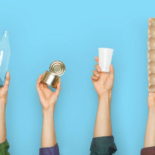 4 Hände die jeweils eine Sache hochhalten. Glasflasche, Konservendose, Pappbecher und einen Eierkarton